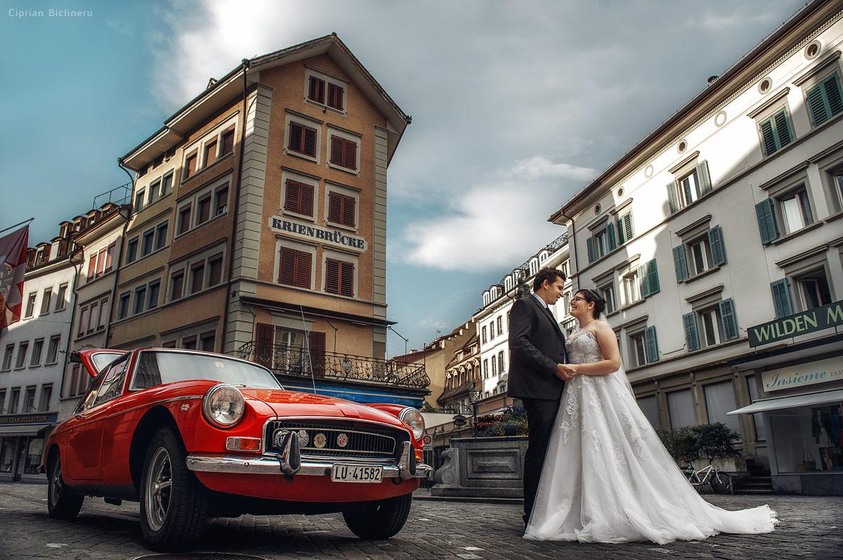Brautpaarshooting in Luzern Schweiz neben einem roten Oldtimer MG Auto