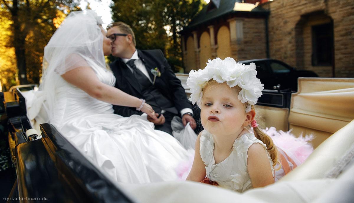 Brautpaar mit Mädchen küssen