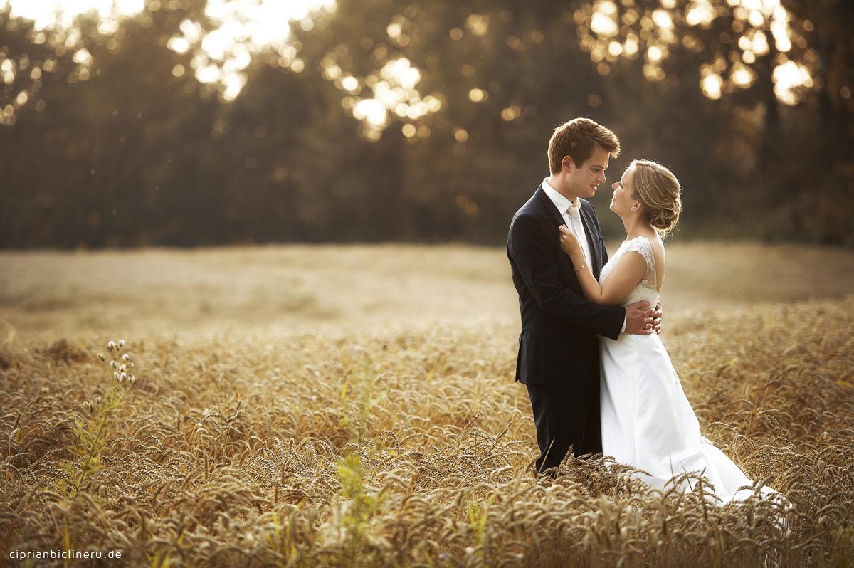 Hochzeitspaar im Feld um Sonnenuntergang