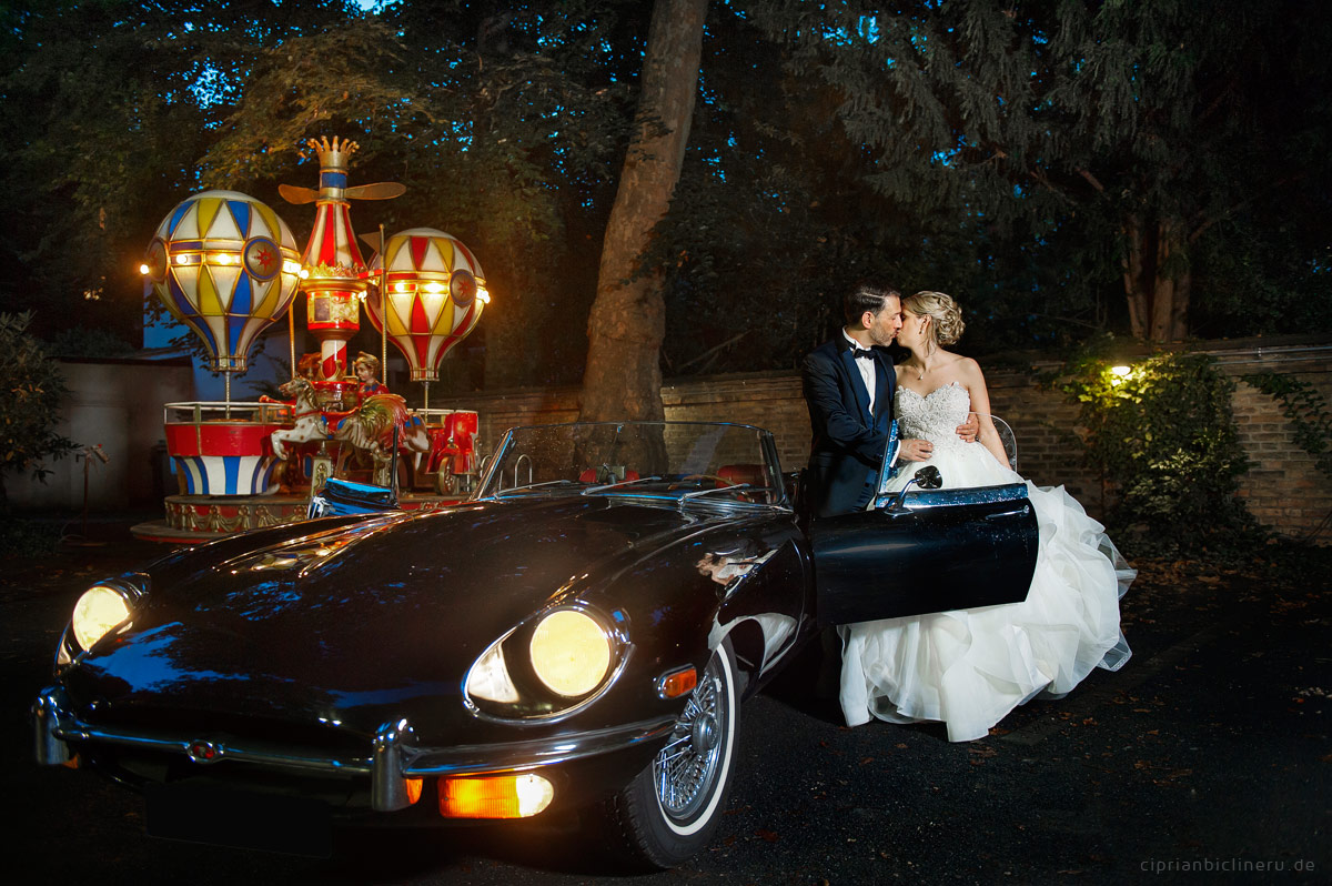 Bride and groom and an old Jaguar at the wedding