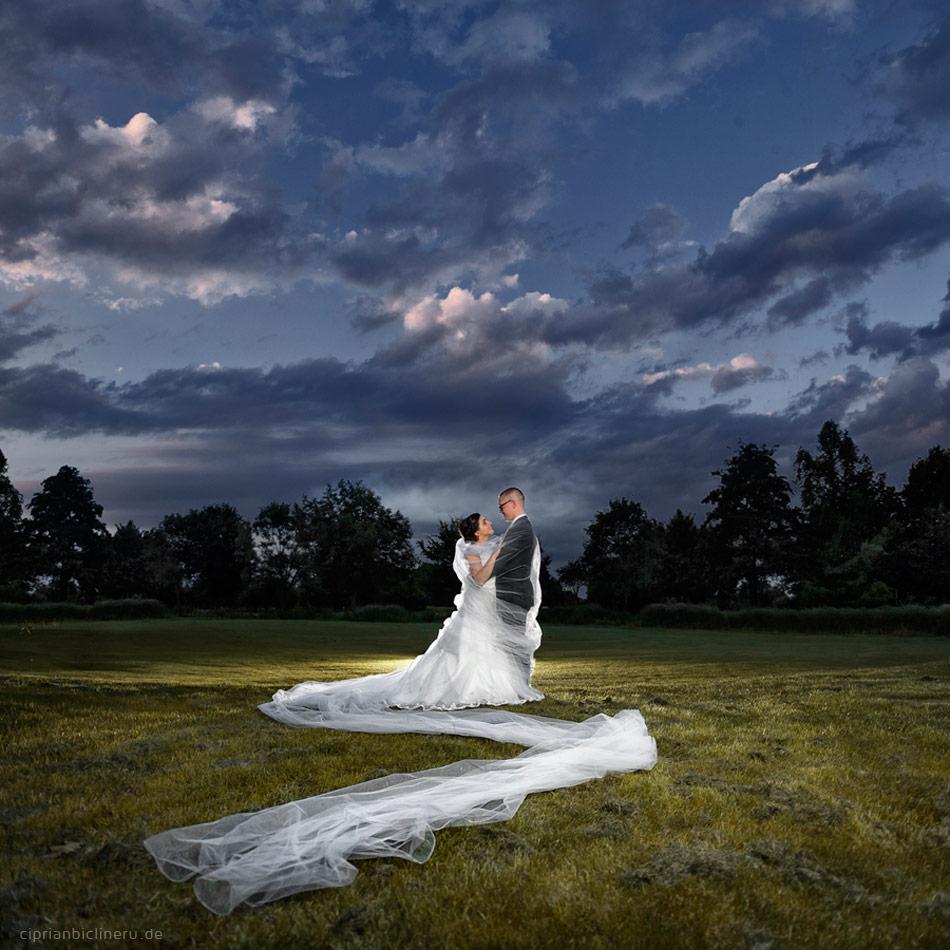 Brautpaarfoto am Abend mit eine sehr langes Schleier